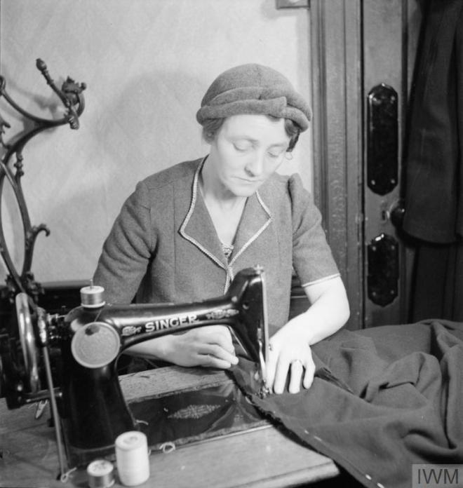 MEND AND MAKE DO: DRESSMAKING CLASSES IN LONDON, 1943 (D 12887) Mrs Bolton at work on a sewing machine during a Make Do and Mend class in the office of the Kennington branch of the Labour Party. She is making a coat for her 16 year old daughter on the sewing machine that she has bought to the class as part of the 'Equipment Pool', to which all members of the class contribute. Copyright: © IWM. Original Source: http://www.iwm.org.uk/collections/item/object/205125908
